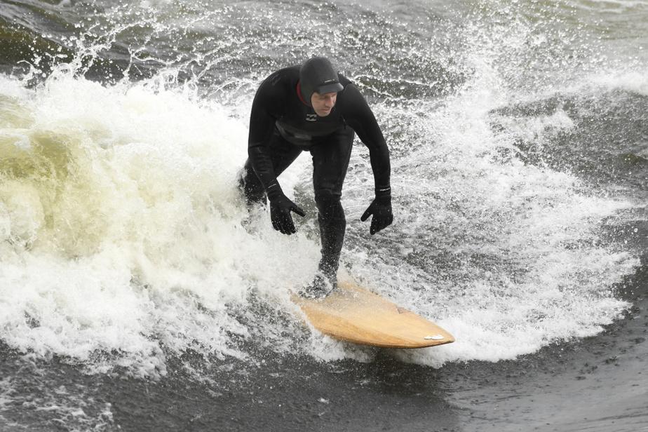 Les surfeurs ont bravé l'eau froide du fleuve Saint-Laurent pour s'élancer sur leur planche à la vague d'Habitat67,au large du parc de la Cité-du-Havre, au sud du Vieux-Port.