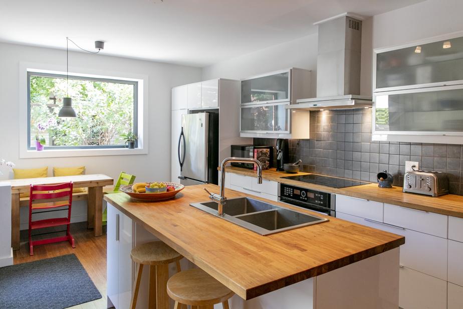 Les armoires de cuisine blanc lustré réfléchissent la lumière naturelle. «Le rez-de-chaussée était sombre avant, mais en créant une aire ouverte et en perçant des ouvertures, il est devenu très lumineux», explique Kristina Joubert, copropriétaire.