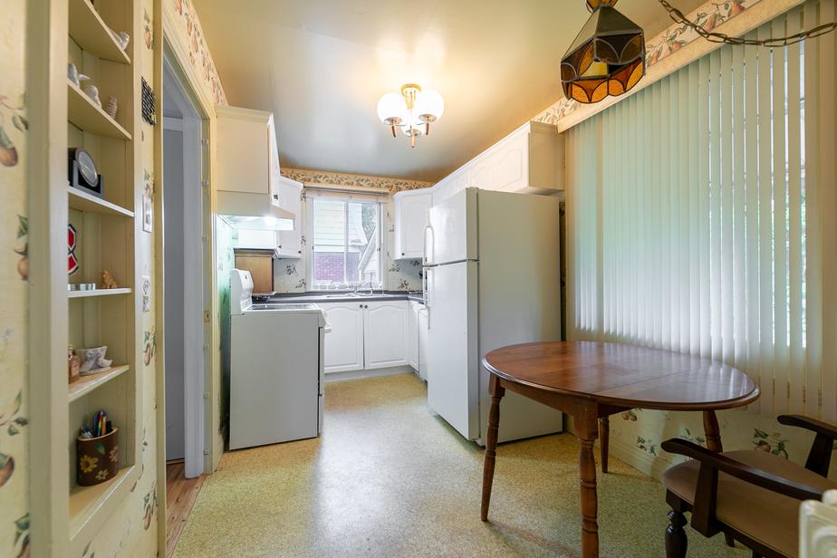 Avant, la cuisine comptait peu de plans de travail. La grande fenêtre à droite a été rapetissée et haussée pour installer un évier et des armoires en dessous. L'espace a été optimisé.