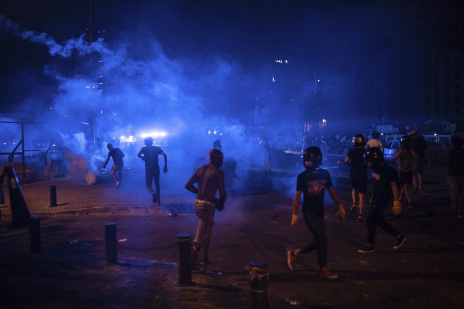 Des manifestants tentent de fuir les gaz lacrymogènes tirés par la police à Beyrouth.