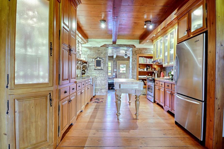 La cuisine a été réaménagée. La pierre et le bois, qui règnent en maître partout dans la maison, se marient ici parfaitement avec l'inox des électroménagers et de l'évier.