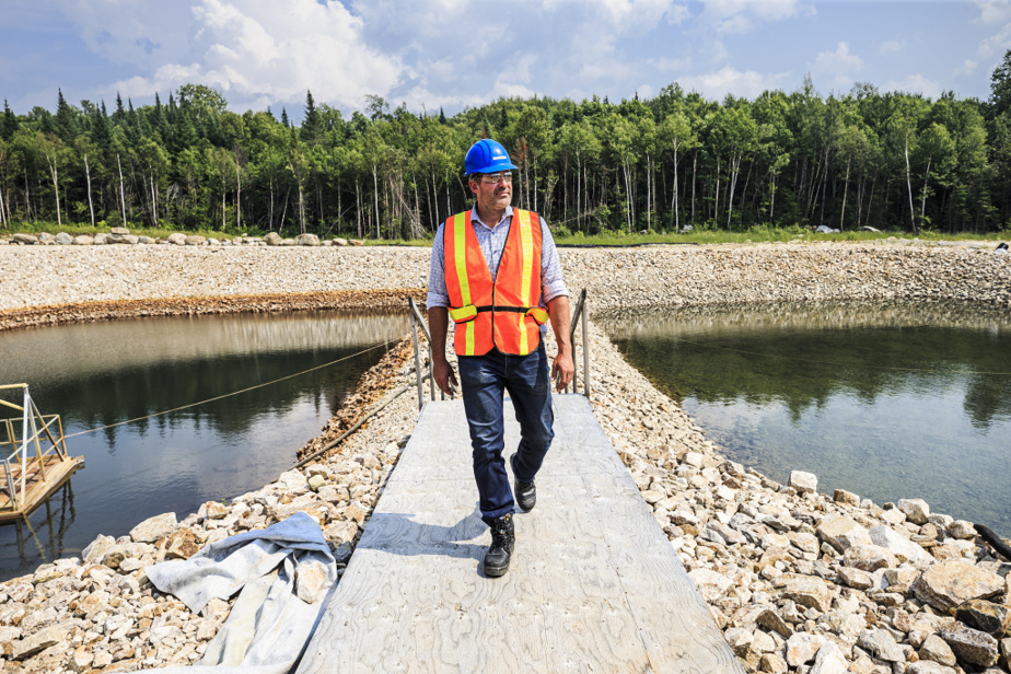 Éric Desaulniers, président-directeur général de Nouveau Monde Graphite, entre deux bassins de collecte des eaux. Celui à droite est plus avancé dans son processus de purification.