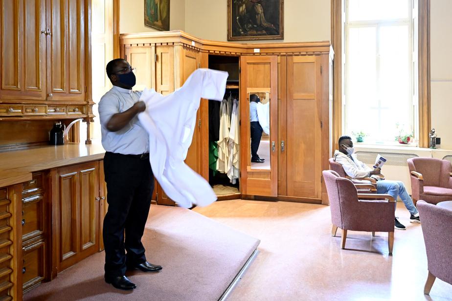 Charles Mangongo enfile son vêtement liturgique.
