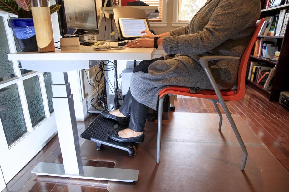 Céline St-Cyr préfère être assise sur une chaise ergonomique avec des pattes droites. Elle ne se passerait pas d'un support pour les pieds. Son bureau, par ailleurs, est à une hauteur adaptée à sa taille.