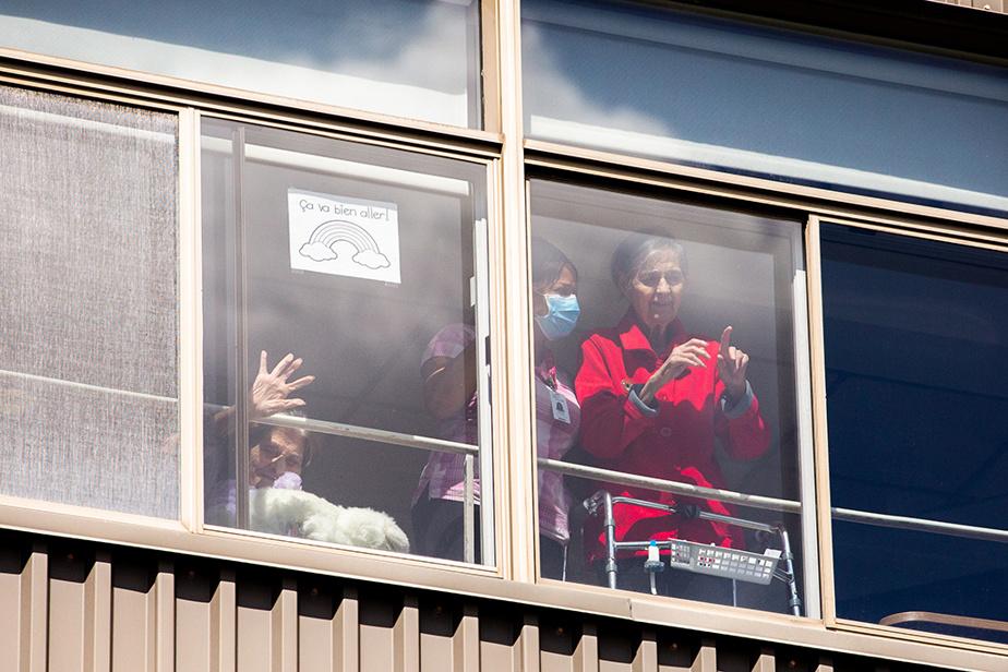 14avril2020. Gilberte Laurin, 88ans, salue son fils qui se trouve à l'extérieur du CHSLD Marie-Rollet à Montréal.