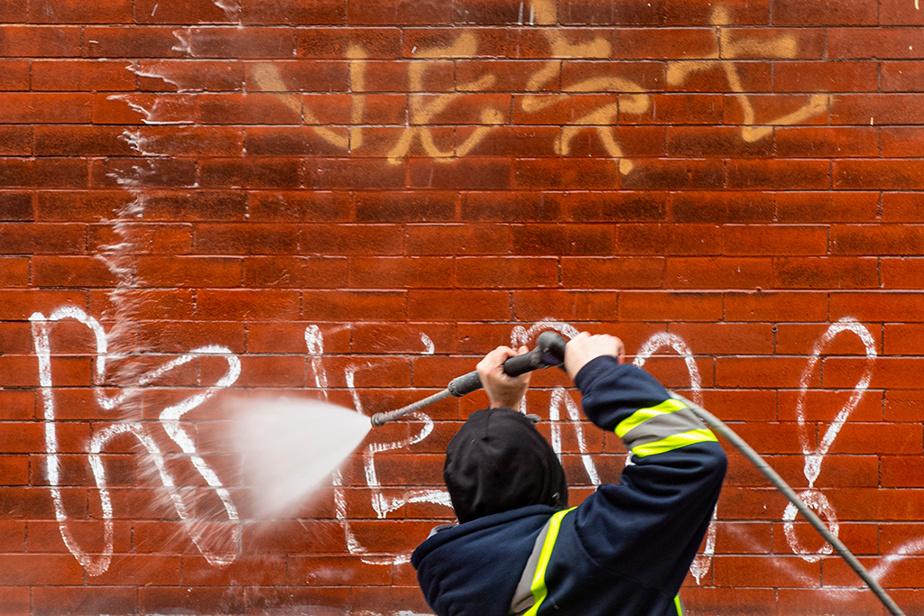 Anthony, un employé de l'entreprise GroupeRNet, nettoie un graffiti sur le mur d'un immeuble résidentiel, àMontréal.