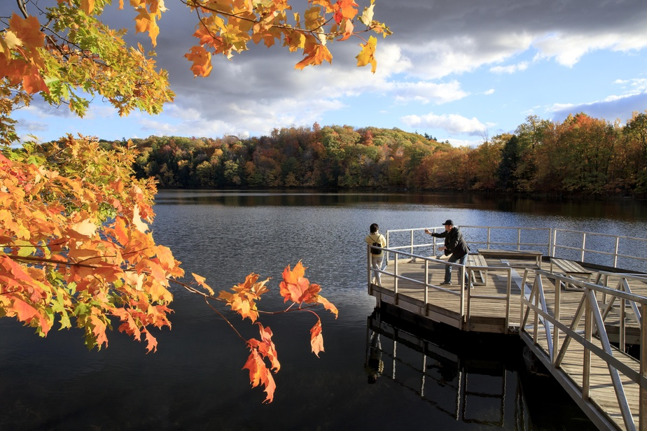 Des visiteurs immortalisent la superbe lumière de fin de journée qui plombe le quai du lac des Bouleaux.