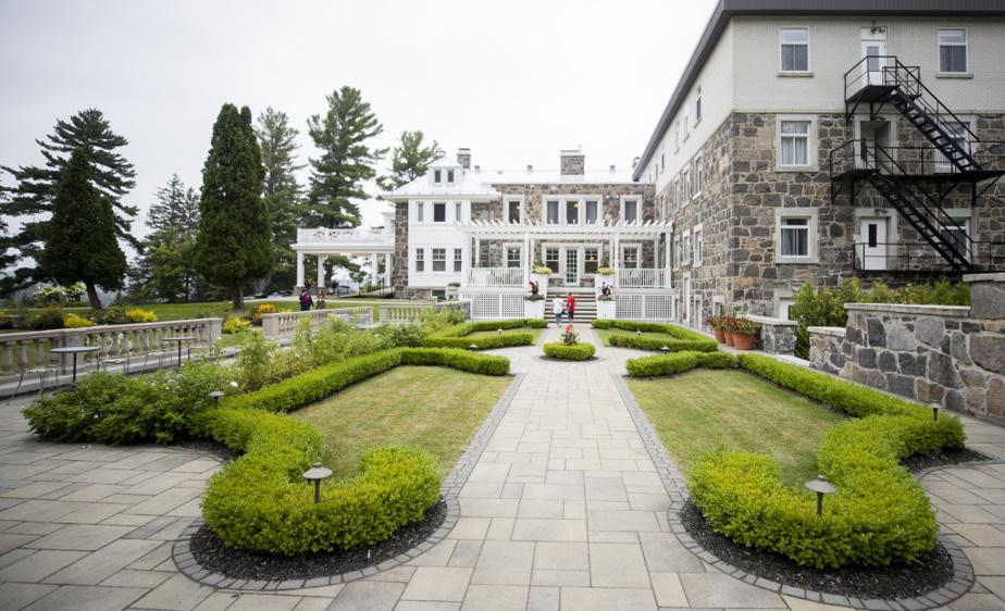 Vue sur les magnifiques jardins et la terrasse situés à l'arrière de la bâtisse, où les clients peuvent prendre un verre et manger.