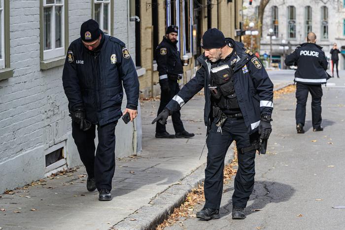 Des policiers et enquêteurs suivent une trace de sang qui pourrait avoir été laissée par l'assaillant ou par une de ses victimes.