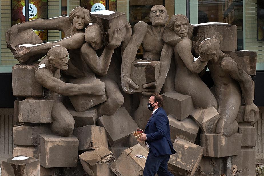 Un passant marche devant la sculpture Les travailleurs et travailleuses, de Roger Langevin, devant l'édifice de la CSN sur l'avenue De Lorimier, à Montréal.