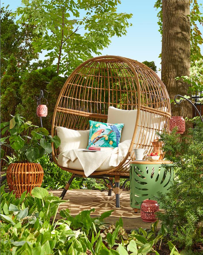 Pour s'évader, un coin fort sympathique a été aménagé au creux du jardin en agençant une chaise tressée en forme d'œuf, un tabouret en métal vert avec un motif végétal, un cache-pot en bambou, des petites lanternes de céramique et un coussin au thème tropical orné de perroquets. De la collection Explorateur du monde, chez Home Depot.