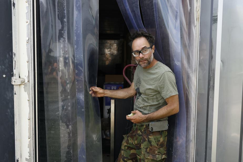 Yan Gordon à l'entrée du conteneur recyclé qui lui sert en alternance de chambre froide, de séchoir à ail et de salle d'entreposage.