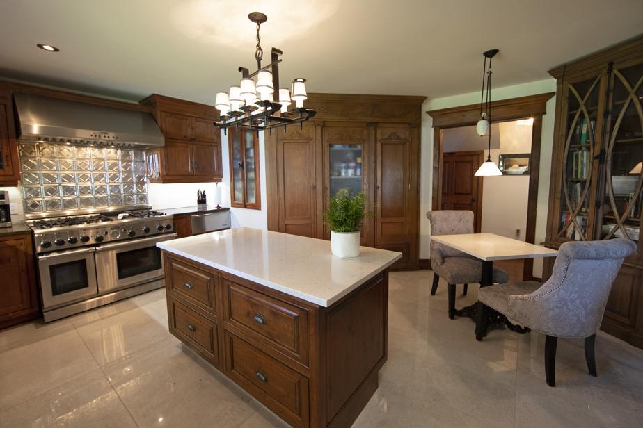La propriétaire adore cuisiner. Elle a conçu un espace pour concocter petits et grands plats. L'armoire au fond est une pièce ancienne qui vient d'un presbytère et qui sert de garde-manger. La cuisinière Thermador compte six brûleurs et une plaque.