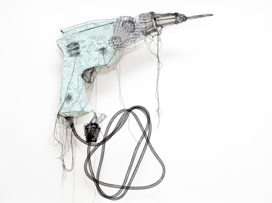 Jannick Deslauriers a utilisé de la dentelle, de la crinoline, de l'organza et du fil pour créer cette perceuse exposée en 2013. Elle tient à ce que les matières qu'elle façonne contrastent avec le thème ou l'objet représenté.