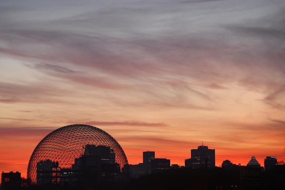 Le coucher de soleil a fait place à un ciel orangé derrière la Biosphère et le centre-ville de Montréal.