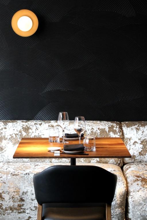 Le design, signé Gauley Brothers, incorpore des murs noirs texturés contrastant avec des banquettes en velours rose doré.