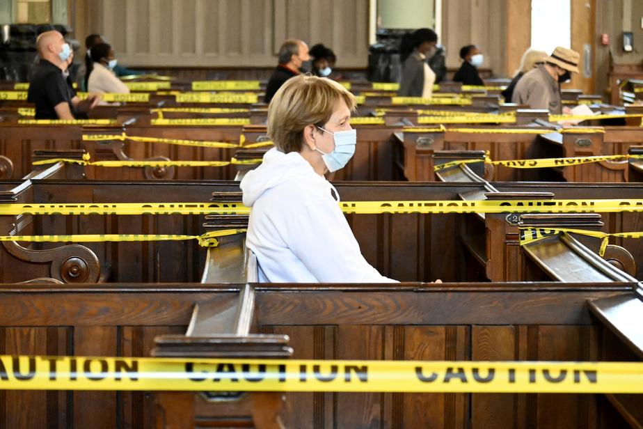 Afin d'assurer la sécurité des croyants et d'éviter qu'ils ne s'assoient sur n'importe quel banc, des rubans jaunes ont été installés. Des bénévoles conduisent les fidèles vers leur place.