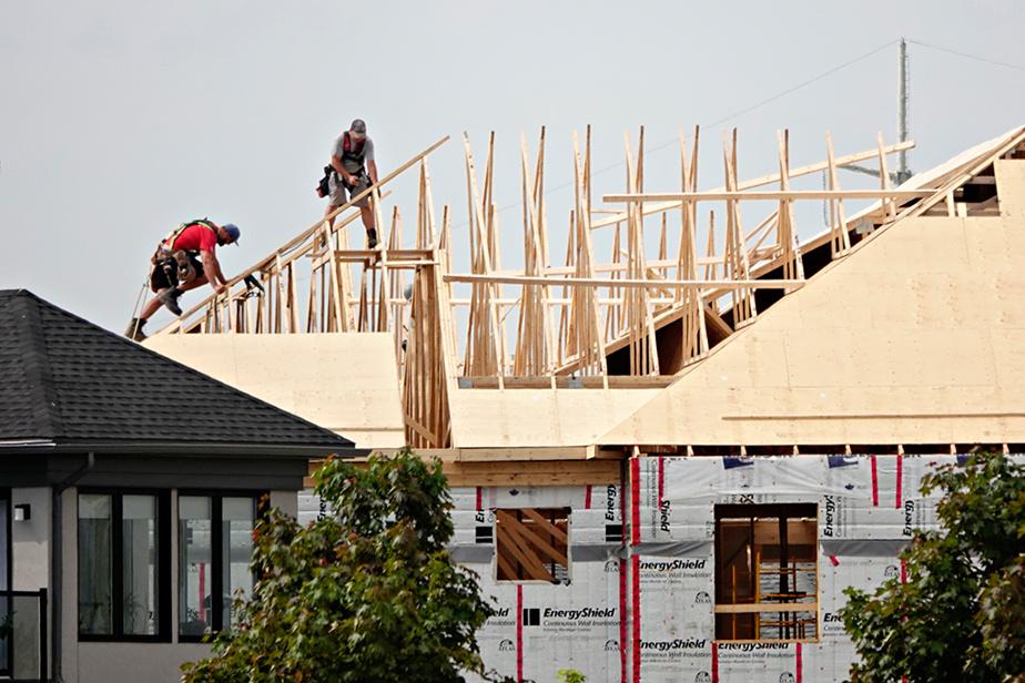 Deux travailleurs de la construction s'affairent à monter un toit sur une maison neuve dans le quartier du Parcours du Cerf, à Longueuil.