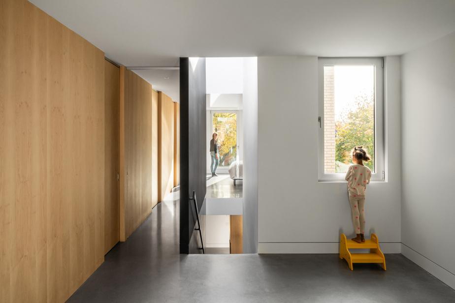 Le mur entre la chambre (au fond) et l'escalier a été laissé vitré, afin de faire parvenir la lumière jusqu'à l'arrière de la maison.