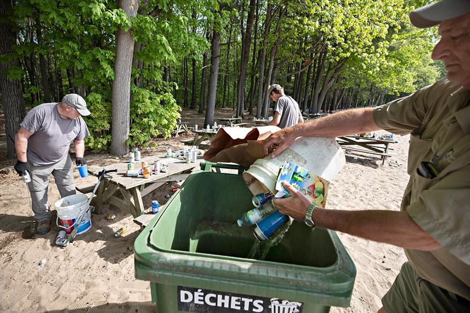 Des employées de la SEPAQ s'affairent à ramasser les contenants d'alcool vides au lendemain d'un rassemblement de 1500personnes tenu la veille à la plage d'Oka, sans distanciation physique.