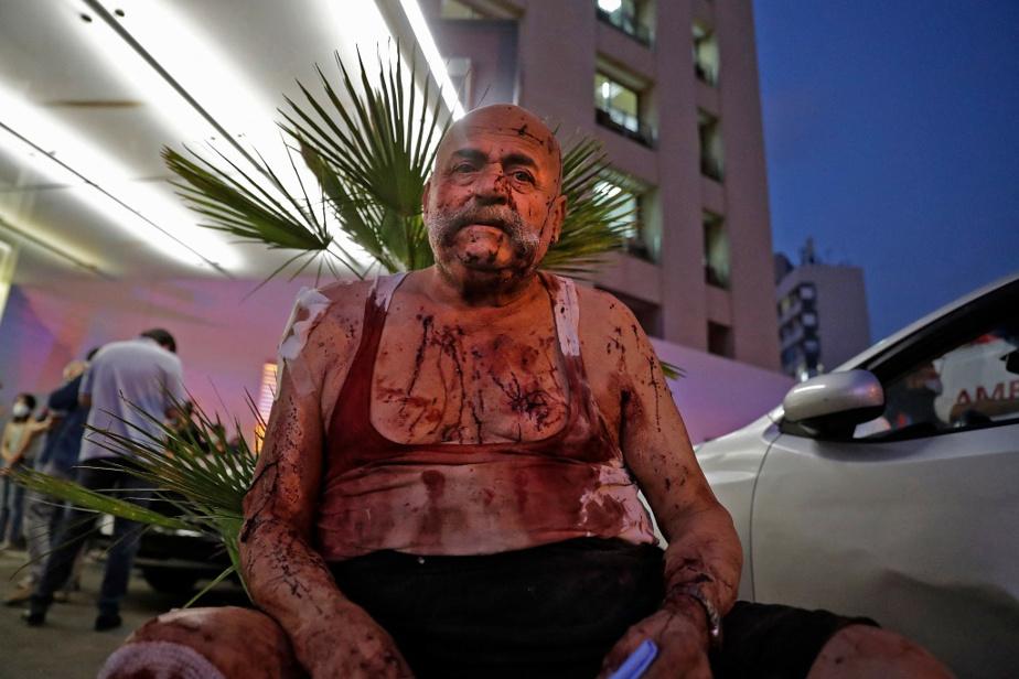 Un homme attend des soins devant un hôpital de Beyrouth lesoir du drame.