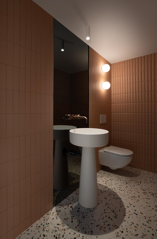 La salle d'eau est élégante avec son verre fumé, son lavabo sur pied, sa robinetterie en cuivre et sa tuile rose capitonnée qui rappelle le cuir.