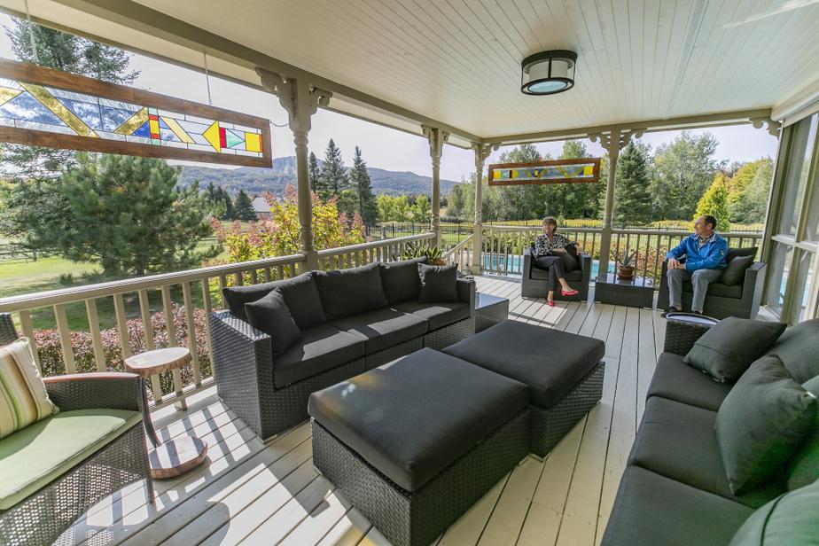 Le couple apprécie aussi ce salon d'été confortable, qui a été couvert afin d'en profiter davantage. Un spa se trouve à l'autre extrémité.