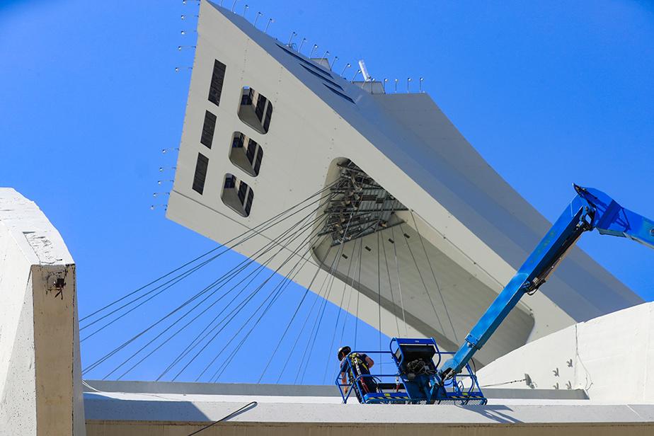 Un homme s'affaire à des travaux de peinture sur le Stade olympique.