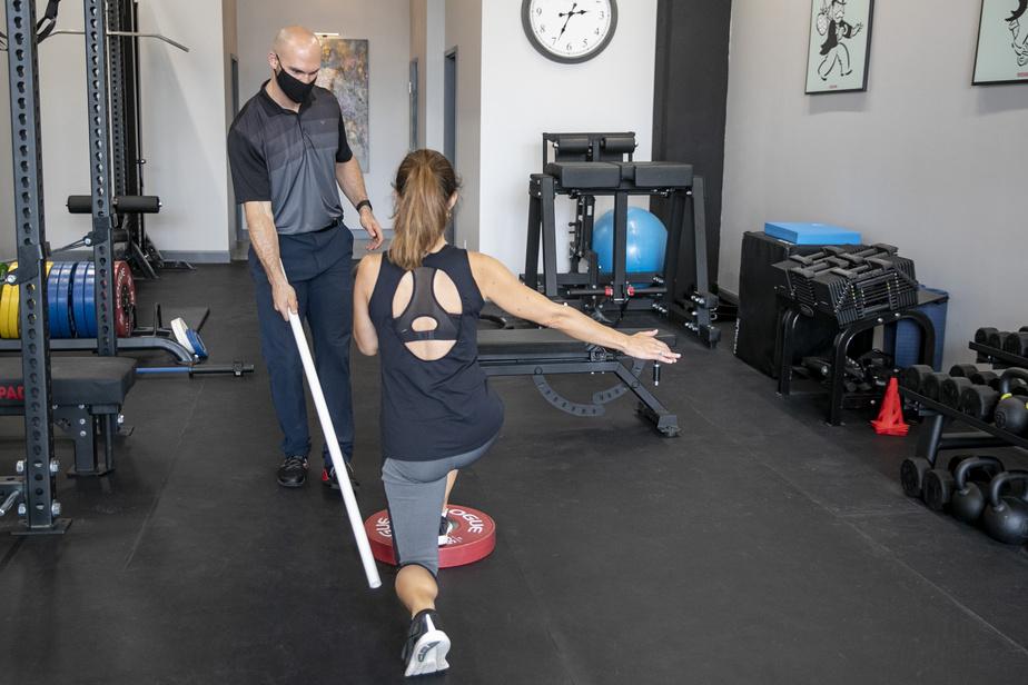 Il suffisait d'y penser: Julien Couvrette utilise un tuyau pour corriger la posture de ses clients, comme ici lors d'un exercice du bas du corps visant à faire travailler les muscles fessiers et les quadriceps.