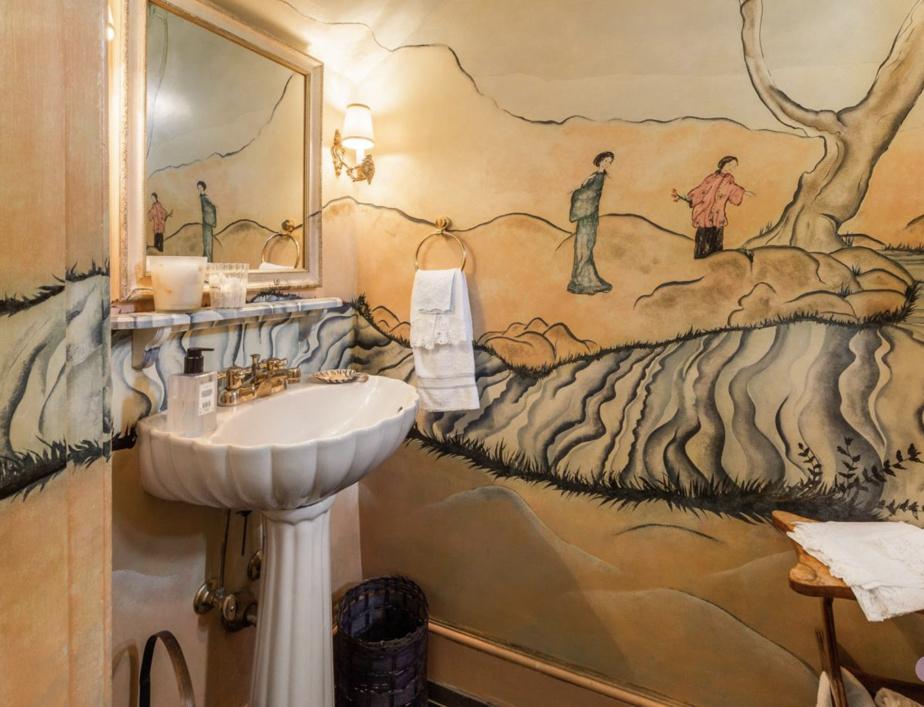 La petite salle d'eau du vestibule a été peinte à la main. Une toile qui représente un paysage.