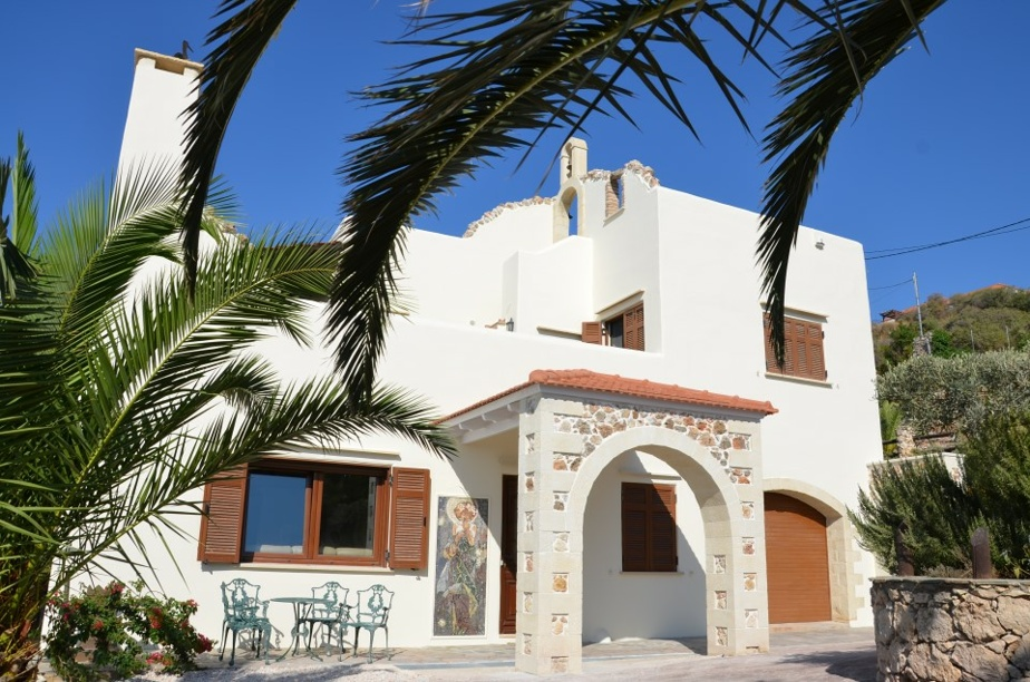 La maison présente des murs d'un blanc éclatant avec mosaïques, pierres intégrées et petit clocher sur le toit.