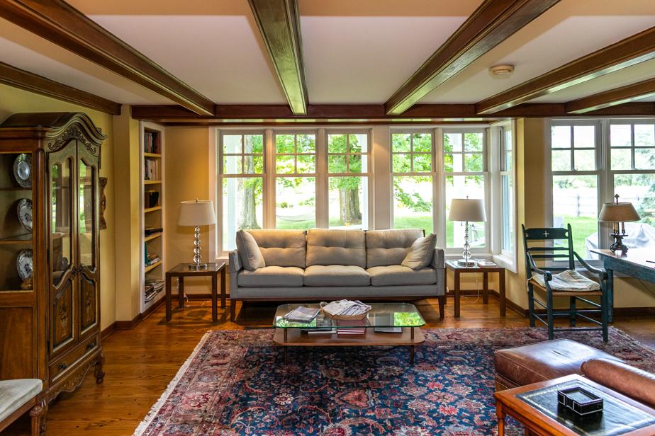 Les propriétaires ont agrandi le salon en y ajoutant une alcôve leur permettant d'y installer un canapé. Cette «extravagance» a obligé leur ébéniste à concocter un assemblage de poutres afin de relier les nouvelles aux anciennes.