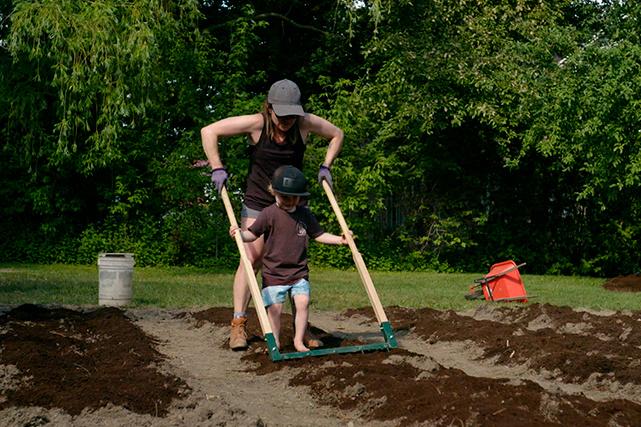 Caroline et son fils préparent le sol à l'aide d'une fourche écologique pour qu'il soit prêt à recevoir les plants.
