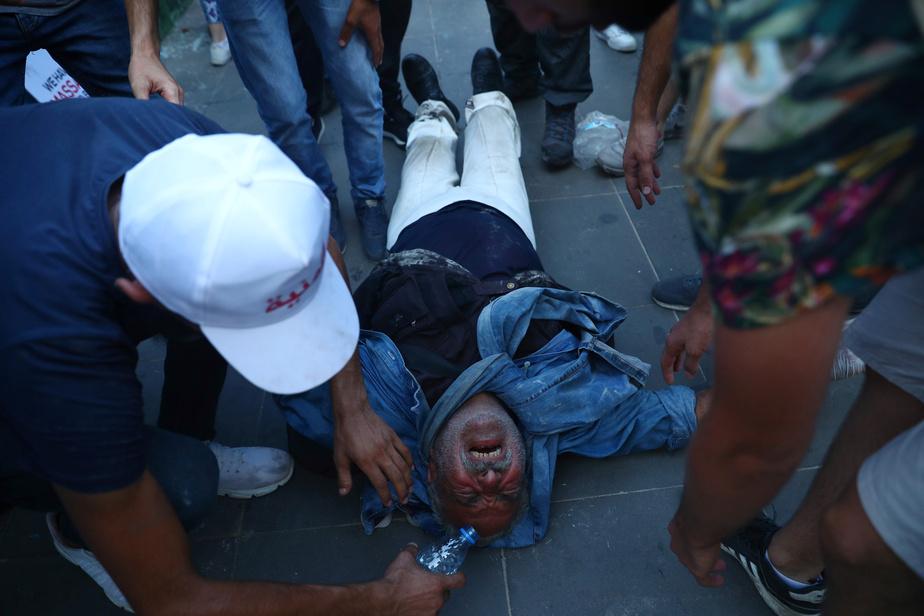 Un homme blessé reçoit l'aide de manifestants.