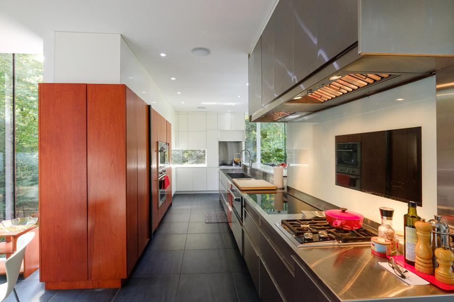 La cuisine hyper équipée, habillée majoritairement d'inox et de bois, inclut plusieurs types de fours et de plaques de cuisson ainsi qu'un chauffe-plats.