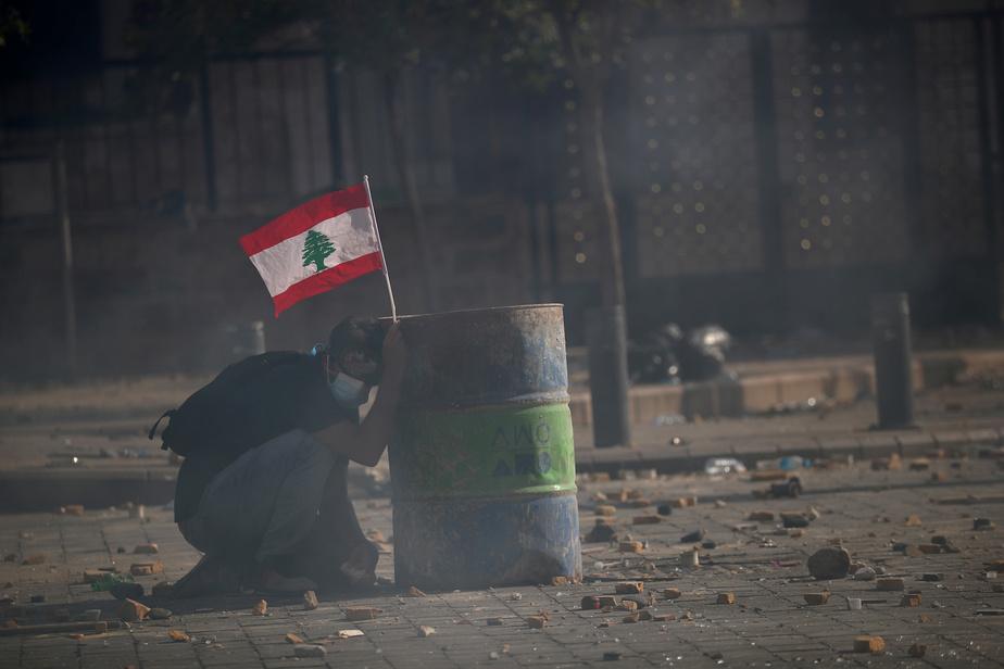 Un manifestant a utilisé un baril comme protection.