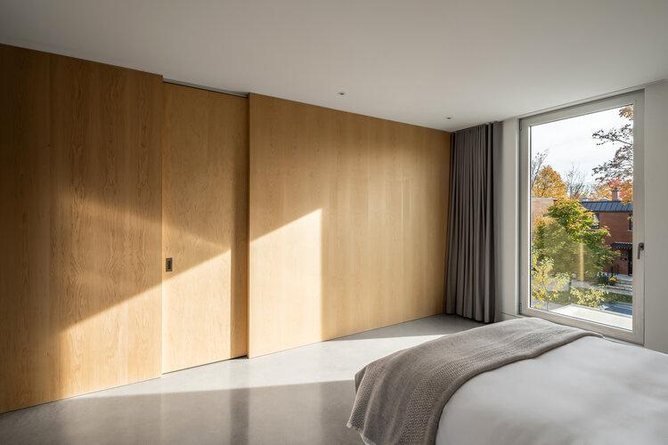 La chambre principale donne sur la rue et reçoit beaucoup de soleil. Une grande cloison de bois cache les espaces de services et de rangement. Partout dans la résidence, le plancher est en béton poli.