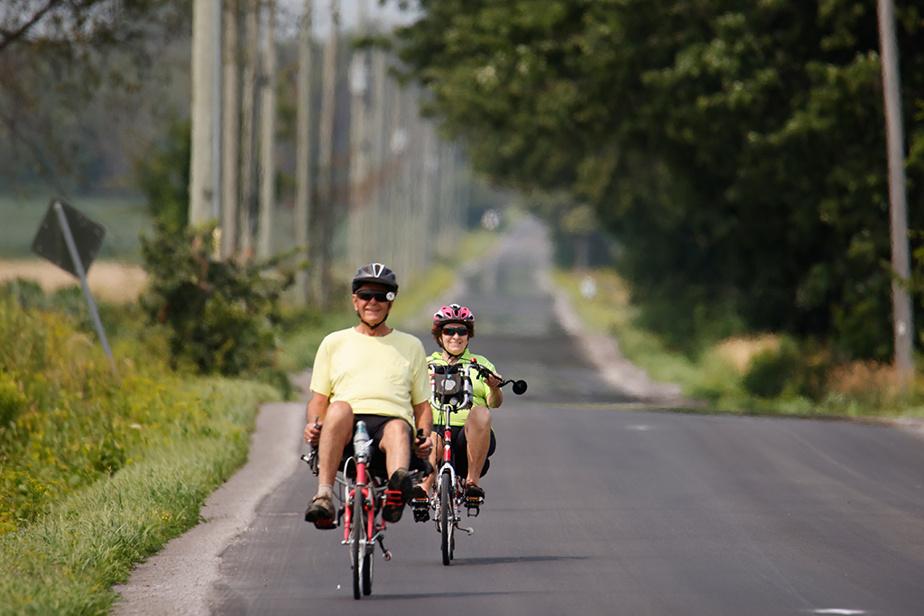 Sur leurs vélos allongés, Richard Patenaude et Louise Lacroix pédalent sur l'asphalte neuf du rang de la Barbotte, à Lacolle.