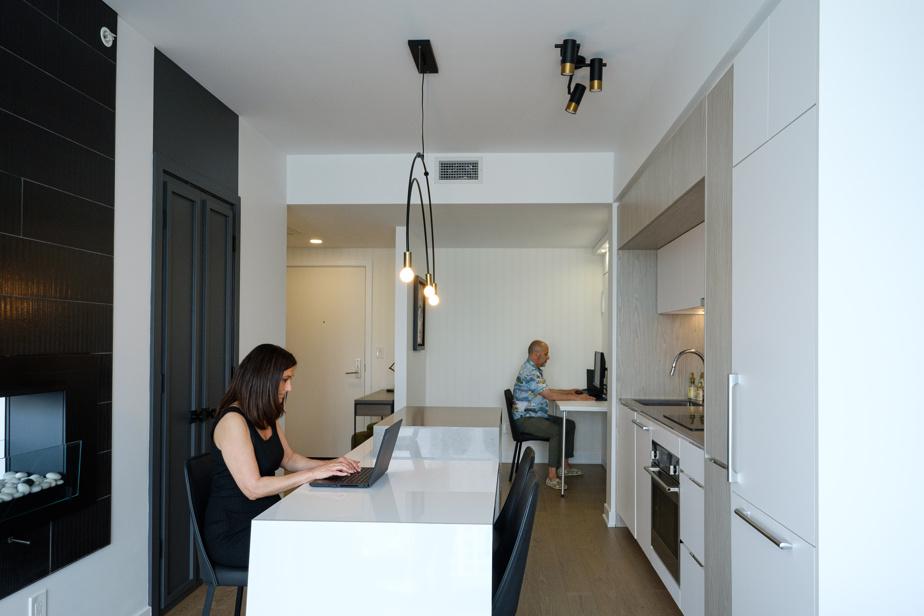 Le couple est parvenu à travailler dans l'appartement sans trop se tomber sur les nerfs. À l'arrière, un lit escamotable est dissimulé dans un meuble qui sert de bureau.