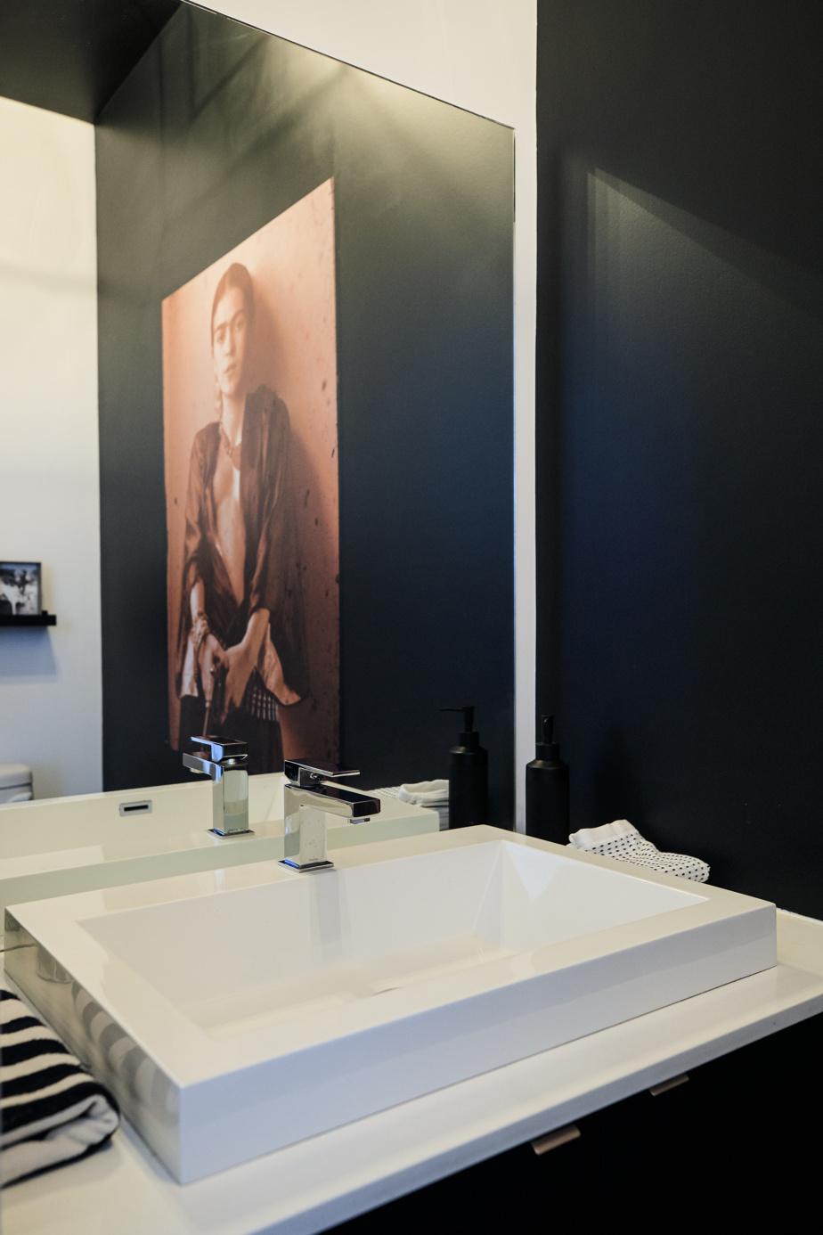 Quand on entre dans la maison, on voit directement la salle d'eau. «Il y avait juste un mur blanc. Le propriétaire est d'origine mexicaine et il aime ce qui vient de son pays d'origine. J'ai proposé de faire quelque chose de théâtral en mettant une image en sépia de Frida Kahlo sur un mur noir. Le plafond est aussi peint en noir, et on y a fixé un bel éclairage. Puis j'ai ajouté une tablette et des objets déco rappelant le Mexique. C'est pas grand-chose, mais ça change tout», explique la styliste et designer Carolina Auz.