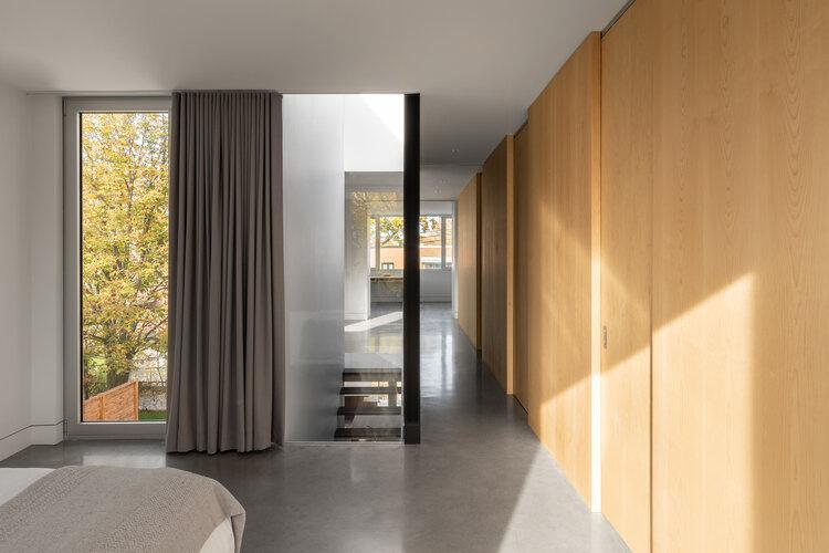 Le renfoncement latéral, le puits de lumière au-dessus de l'escalier ainsi que les grandes fenêtres en façade rendent très lumineux le volume plutôt étroit et profond.