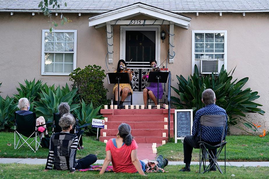 Le duo Masked Strings (les cordes masquées), composé des violonistes Nancy Kuo (à gauche) et Manoela Wunder, offre un concert intime à ses voisins, dans le quartier Atwater Village, à Los Angeles, le 30 août.