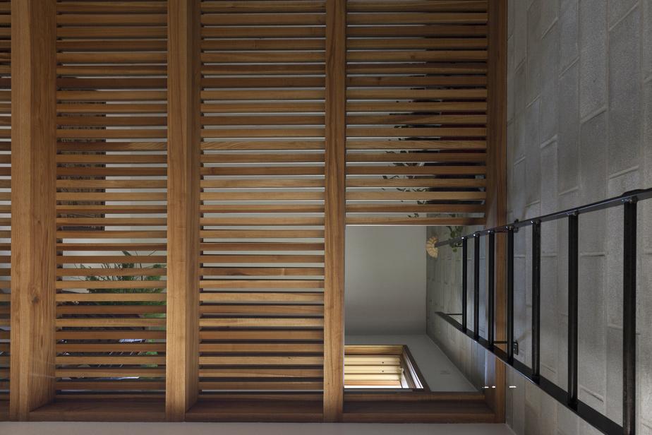 En bois ajouré, le plancher de l'étage allège l'espace et laisse passer la lumière sur les deux niveaux.
