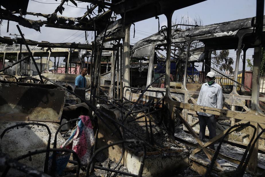 Lagos est néanmoins marqué par des jours de violences. Sur la photo, des habitants observent la carcasse d'autobus brûlés.