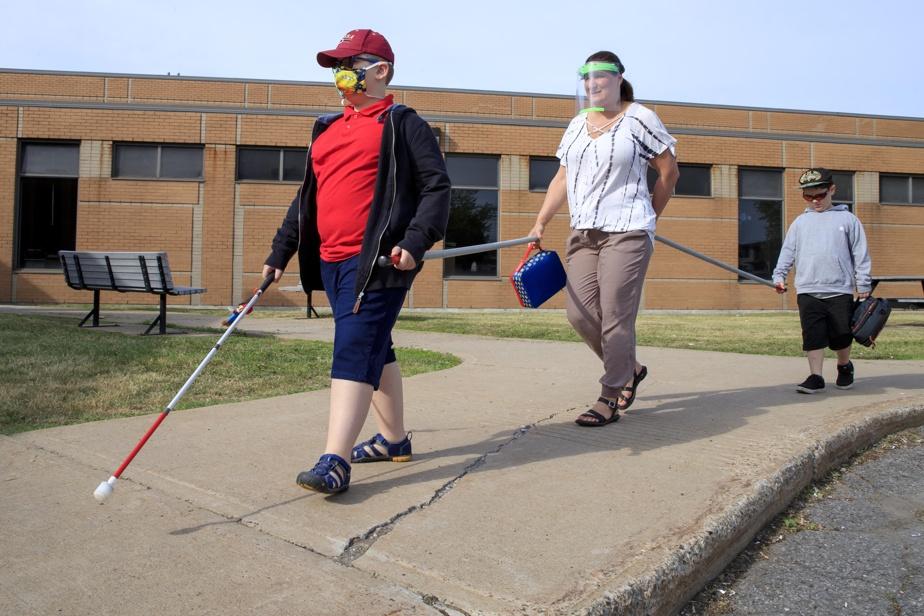 10juin2020. L'école Jacques-Ouellette est un établissement d'apprentissage pour enfants aveugles. En pleine pandémie, l'école a trouvé le moyen de fonctionner tout en respectant les directives de la Santé publique, comme le prouve l'éducatrice Josée Loisel, qui fait une promenade avec Marc-Antoine et Gabriel.