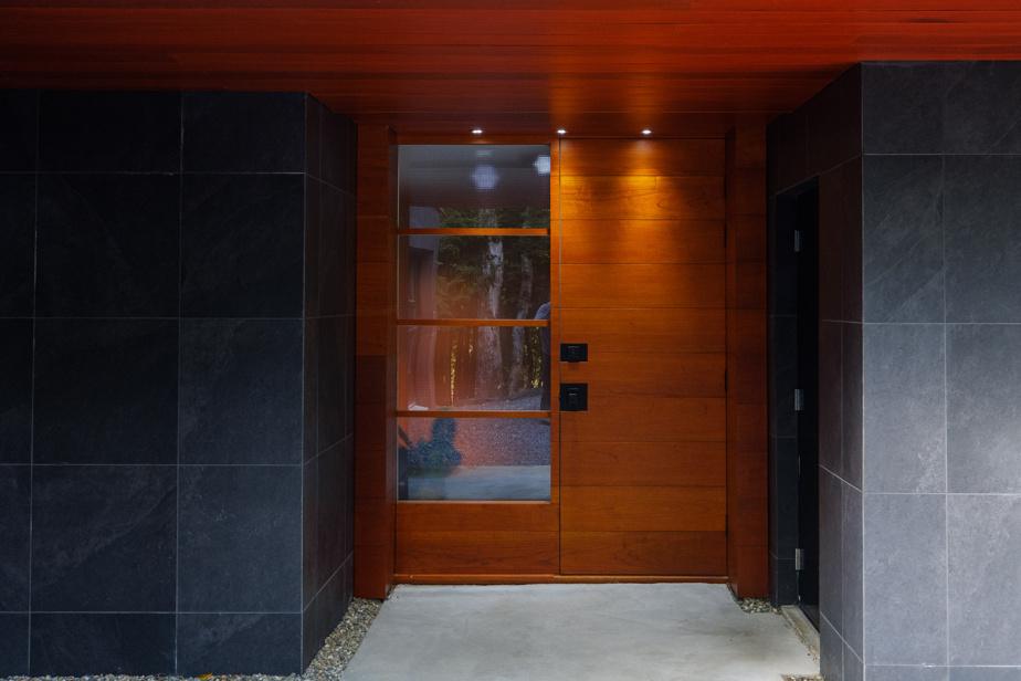Le propriétaire est très fier de sa porte d'entrée, à la fois cossue, minimaliste et de grande qualité. Il l'a réalisée avec son ébéniste, comme toutes celles à l'intérieur de la maison.