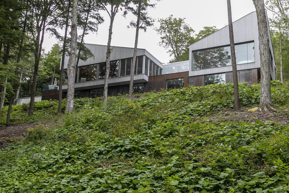 Le rez-de-jardin est recouvert d'acier et s'efface pour donner l'impression que le haut de la maison est en suspension au-dessus du terrain.