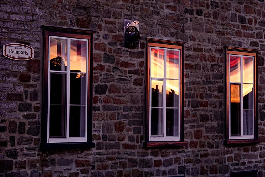 Le soleil couchant est reflété dans les fenêtres d'un immeuble de la rue des Remparts, dans le Vieux-Québec.