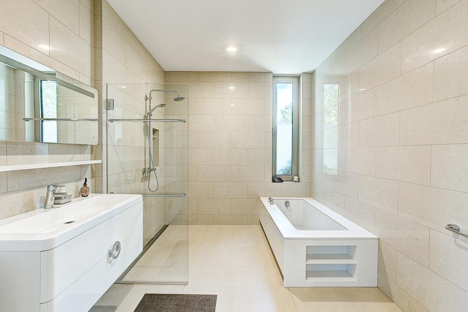 Sobre et zen, la salle de bains des maîtres, à l'instar de celles du rez-de-jardin, est équipée d'une douche à l'italienne.