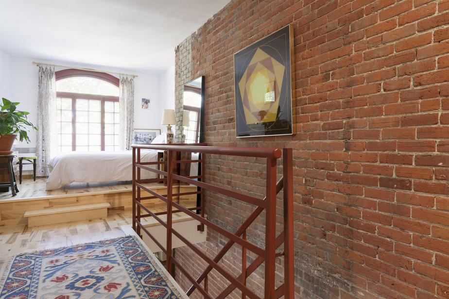 L'escalier en fer mène à la chambre, baignée de lumière.